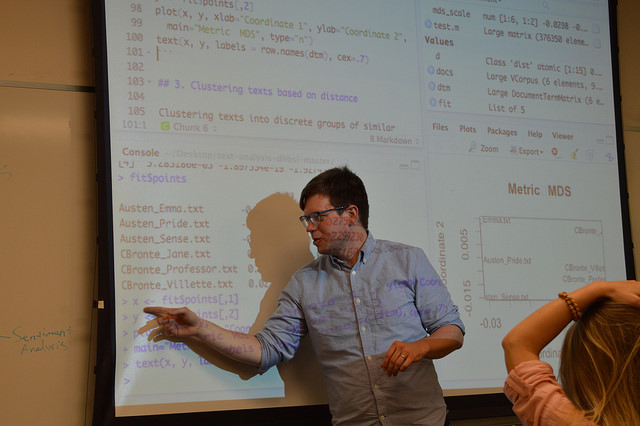Teddy Roland teaching | Demo code from R Studio projected behind him
